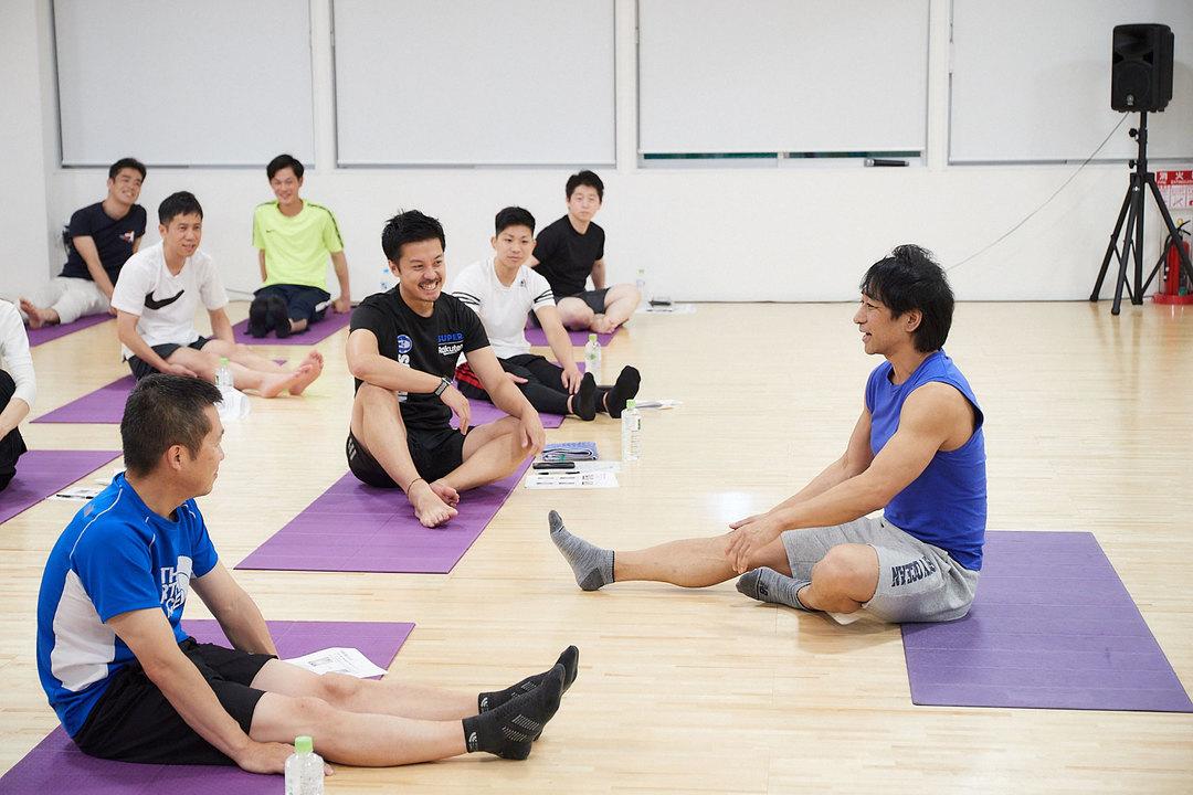 参加者とコミュニケーションを取りながら体前屈を実演する坂詰さん。